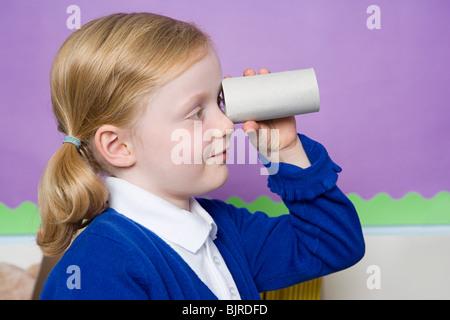 Girl looking through toilet roll - Stock Photo