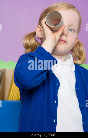 Girl looking through a toilet roll - Stock Photo