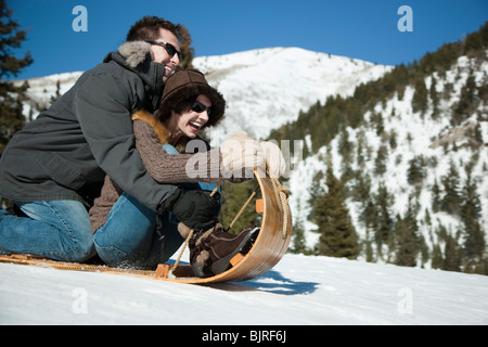 USA, Utah, Big Cottonwood Canyon, couple tobogganing in mountains - Stock Photo