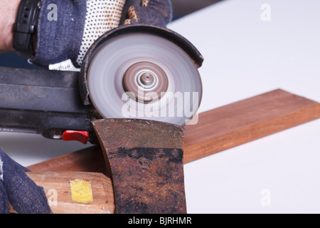 An angle grinder being used to sharpen the blade of an axe. - Stock Photo