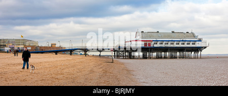 Man walks a dog along the beach near the Pier 39 on Cleethorpes beach, Lincolnshire England UK in winter - Stock Photo