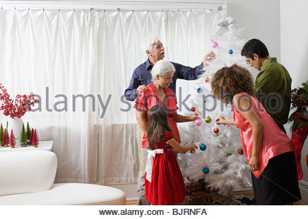 A family decorating a christmas tree - Stock Photo