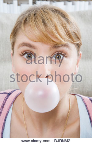 Portrait of a teenage girl blowing bubble gum - Stock Photo