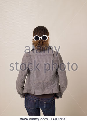 Rear view of a teenage girl wearing sunglasses - Stock Photo