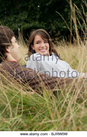 Young couple relaxing in a field - Stock Photo