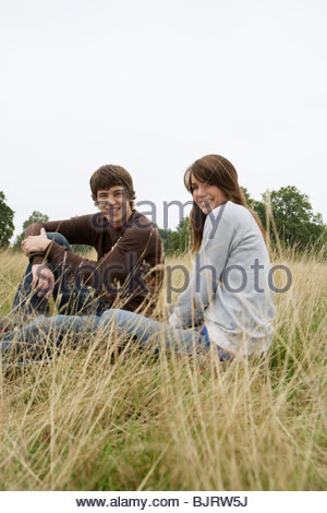 Young couple sitting in a field - Stock Photo