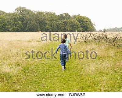 Two children walking in a field - Stock Photo