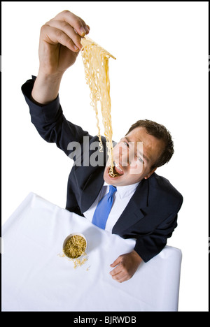 Businessman awkwardly eating noodles - Stock Photo