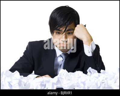 Frustrated businessman surrounded by crumpled papers - Stock Photo
