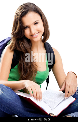 Beautiful young female student sitting on floor studying, isolated on white - Stock Photo