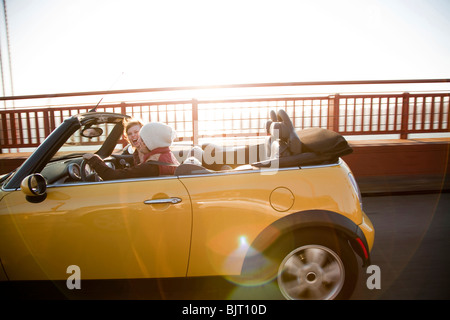 USA, California, San Francisco, young couple sitting car with Golden Gate Bridge in background, portrait - Stock Photo