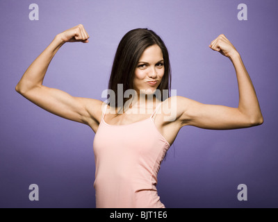 Woman flexing her biceps - Stock Photo