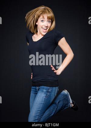 Young cheerful woman jumping, studio shot - Stock Photo