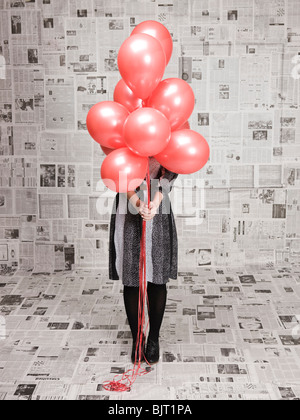 Young woman hiding face behind bunch of balloons in newspapers covered room, studio shot - Stock Photo