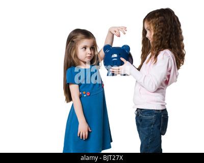 Studio shot of girl (4-5) inserting money to piggy bank held by sister (6-7) - Stock Photo