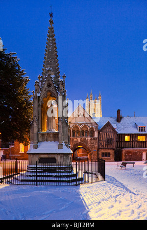 Dusk falling on winter snow at Bishop Hooper's Monument in St Mary's Square beside Gloucester Cathedral - Stock Photo
