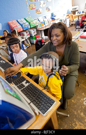 Detroit, Michigan - First grade teacher Ivy Bailey teaches computer use at MacDowell Elementary School. - Stock Photo