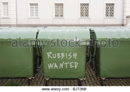 Graffiti on green wheelie bins - Stock Photo
