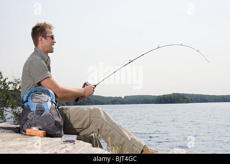 Man fishing in lake - Stock Photo