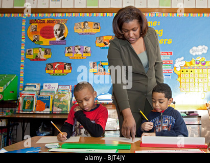 Detroit, Michigan - First grade teacher Ivy Bailey helps two students at MacDowell Elementary School. - Stock Photo