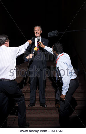 A politician being interviewed by reporters - Stock Photo