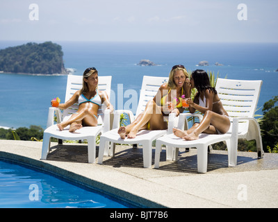 Three women relaxing on deck loungers - Stock Photo