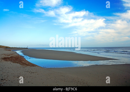 Horsey beach, Norfolk, England, United Kingdom, with small pool and reflections left by an ebbing tide. - Stock Photo
