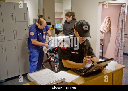 Emergency medical technicians, one of them a registered nurse (background, left), fill out paperwork at  radiology - Stock Photo