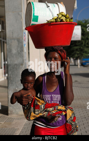 Portrait of a young mother street seller carrying a baby and a bucket on her head. Benguela city, Angola. Africa. - Stock Photo