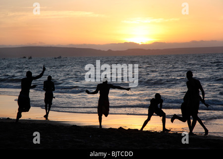 Friends playing football on the beach as the sun sets. Benguela city beach, Angola. Africa © Zute Lightfoot - Stock Photo