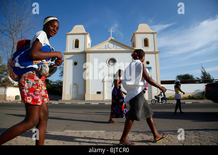 Women carrying their children past a church in the bay of Namibe, Namibe Province, Angola, Africa - Stock Photo