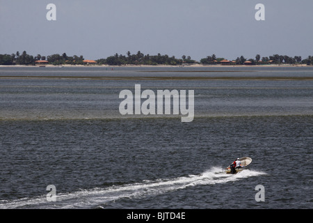 Speedboat travelling across the bay to Mussulo sand spit. Beaches and holiday home of wealthy Luandan's. Mussulo, - Stock Photo