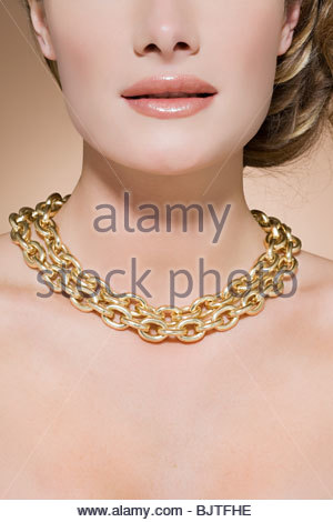 Woman wearing a gold necklace - Stock Photo
