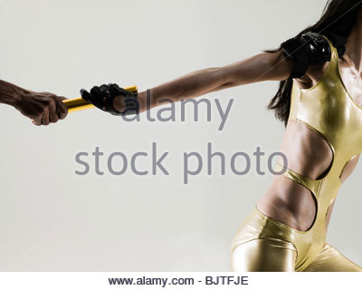 Runners passing a relay baton - Stock Photo