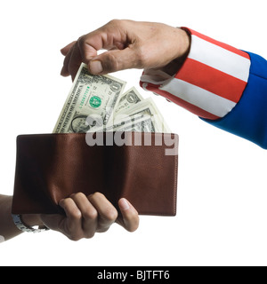 Man in Uncle Sam's costume taking money from wallet, studio shot - Stock Photo