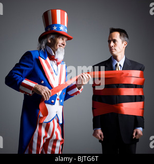 Man in Uncle Sam's costume wrapping other man with ribbon, studio shot - Stock Photo