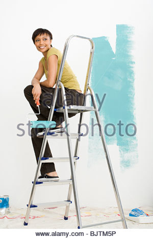 Woman on stepladder - Stock Photo