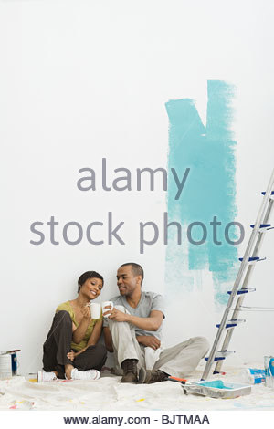 Couple taking a break from painting - Stock Photo