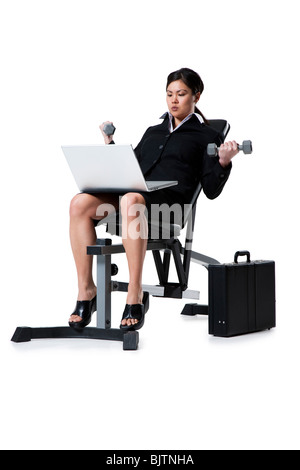 Woman with laptop lifting dumbbells - Stock Photo