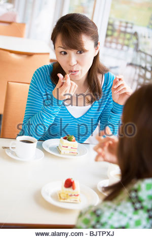 Two women eating cake at a cafe - Stock Photo