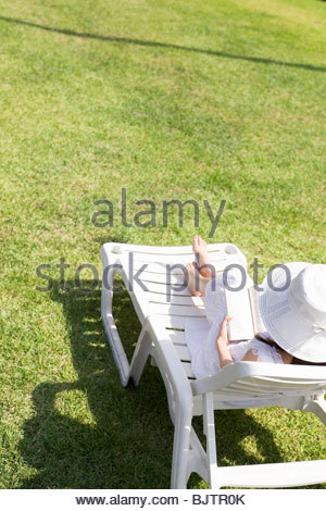 Young woman reading book on a deck chair in backyard - Stock Photo