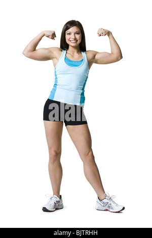 Woman flexing biceps and smiling - Stock Photo