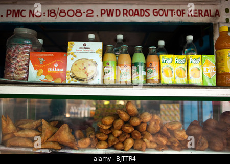 India, Kerala, Palakkad, samosas, cutlets and soft drinks on display at roadside snack stall - Stock Photo