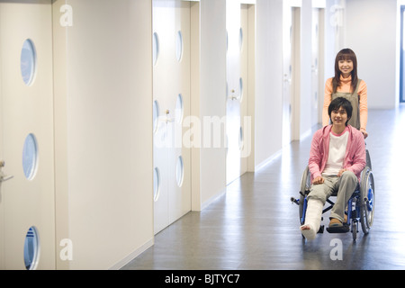 Woman pushing her boyfriend who is in a wheelchair - Stock Photo