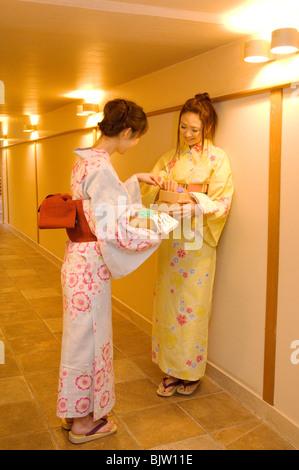 Women wearing yukata standing talking in hallway of health spa - Stock Photo