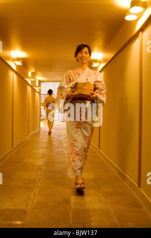 Two women wearing yukata walking through the corridor of a health spa - Stock Photo
