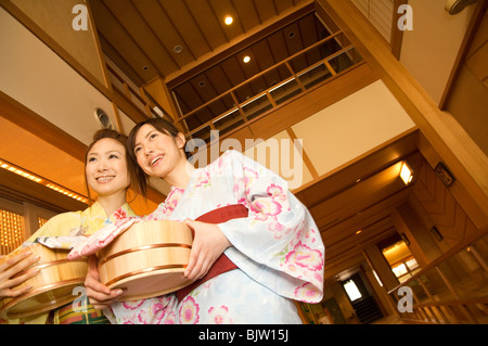 Two women wearing yukata and holding spa products at a health spa - Stock Photo