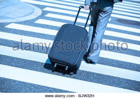 Businesswoman on zebra crossing with suitcase - Stock Photo