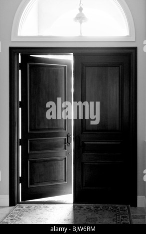 Black and white image of large dark wooden entry doors with arched window above - Stock Photo