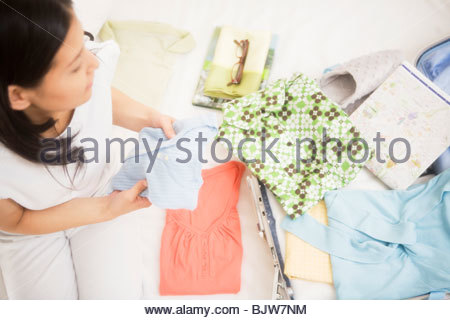 Woman packing her suitcase - Stock Photo